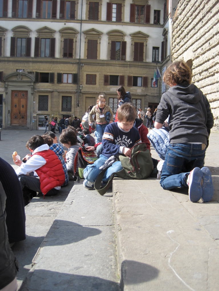 Waiting alongside a group of school children. They were eating mortadella sandwiches, and I got hungry watching them eat
